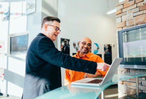 A business owner pointing to a laptop in front of his client.