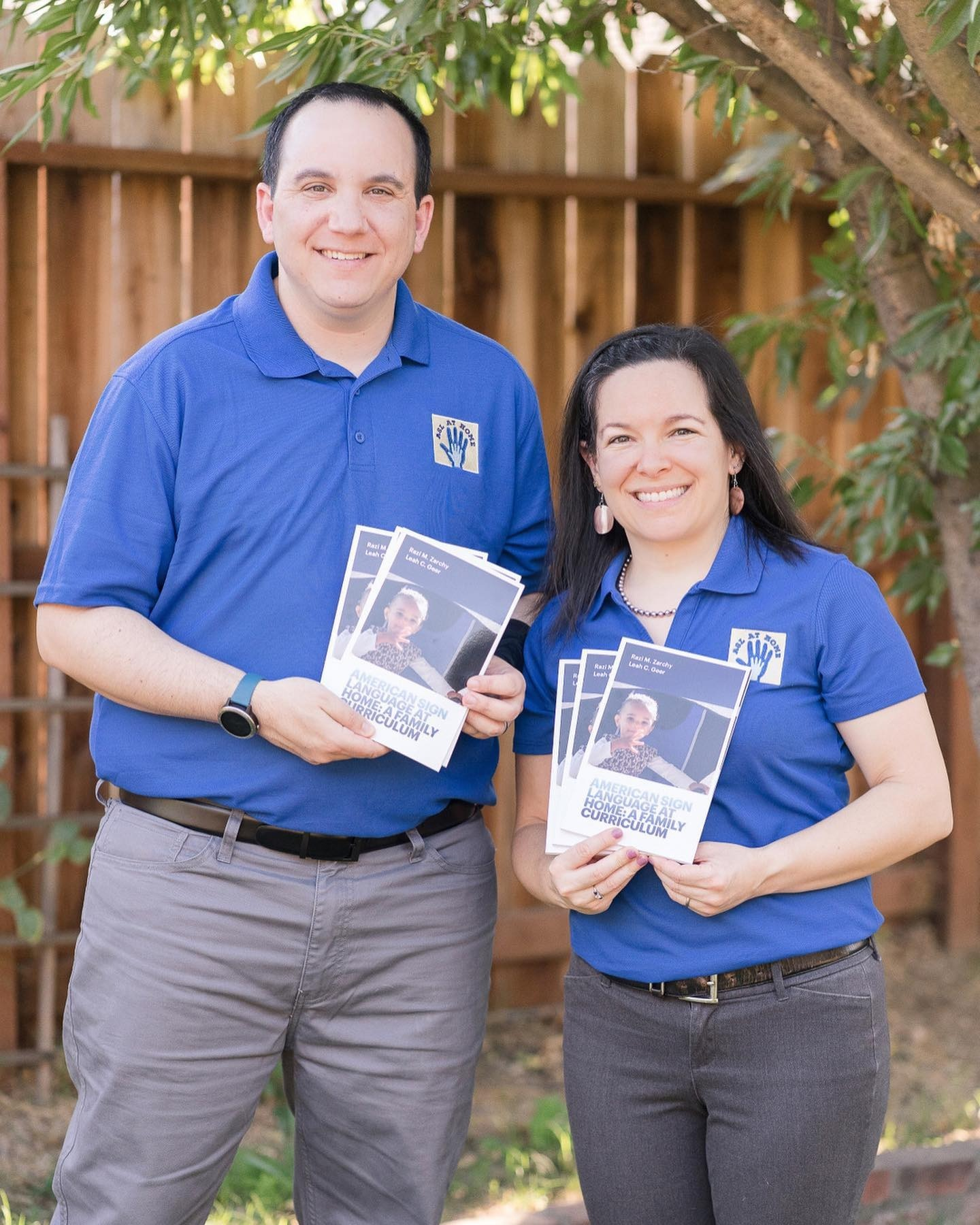 Razi and Leah standing together, wearing blue ASL at Home polo shirts and holding up several print copies of their book