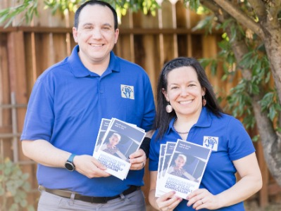 Razi and Leah standing in front of a tree, wearing ASL at Home polo shirts and holding up several copies of the ASL at Home book