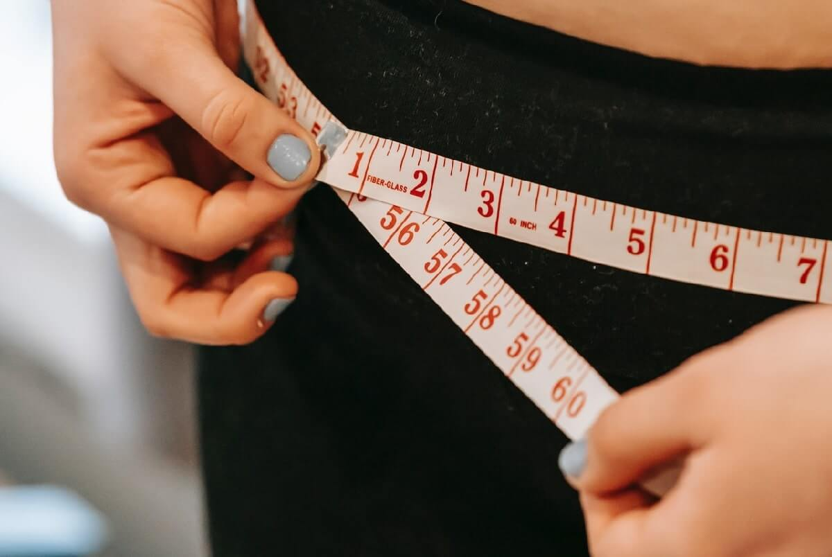 woman measuring belly with tape. Okinawa Flat Belly Tonic